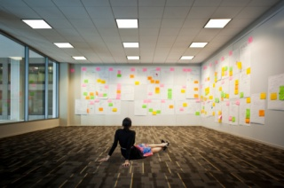 Woman sitting on floor looking at wall of ideas